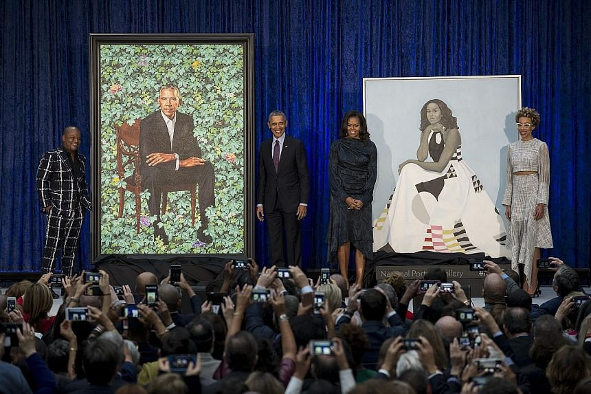 Former United States president Barack Obama and his wife Michelle (both centre) with their official portraits by artists Kehinde Wiley (left) and Amy Sherald (right).