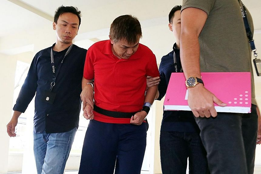Suspected loan-shark runner John Tong Leok Han, 49, was escorted by police back to the scene of his alleged crime at Block 309, Tampines Street 32, yesterday. Tong was charged in court last Saturday over a case of aggravated unlicensed moneylending h