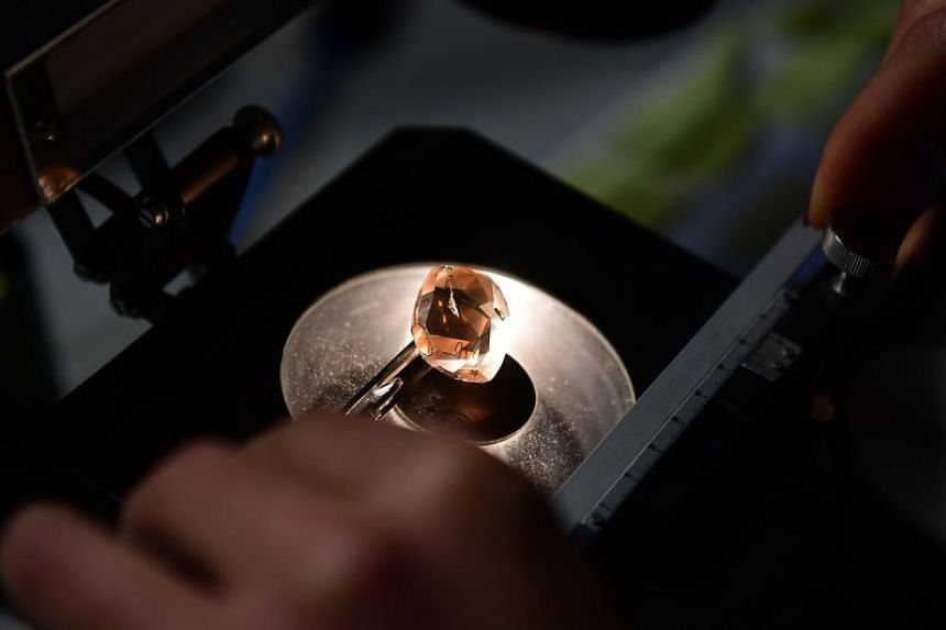 A diamond expert studies a diamond under an electronic microscope at Simply Sparkling, a company specialized in advanced technological diamond manufacturing, transforming rough diamonds into polished stones, in Antwerp.