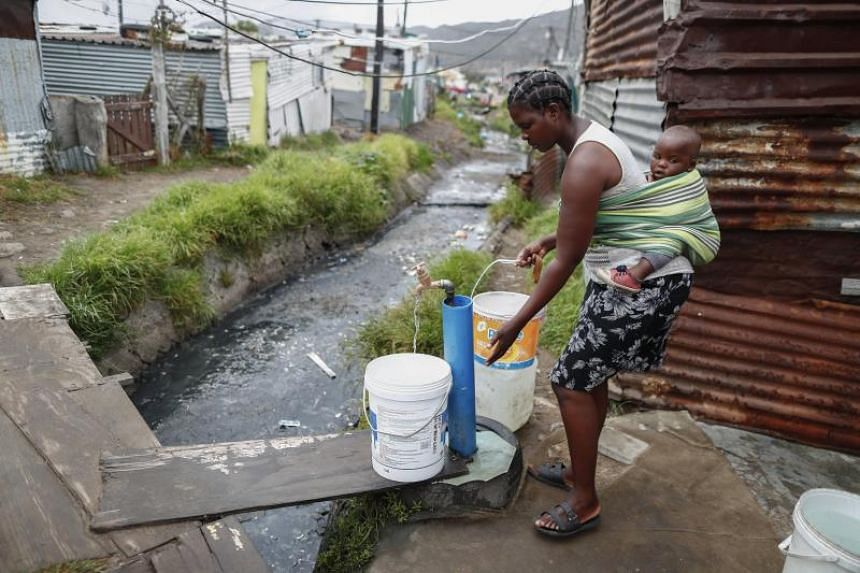 A resident of Masiphumelele informal settlement collects drinking water from a communal municipal tap in Cape Town, South Africa, on Jan 30, 2018.