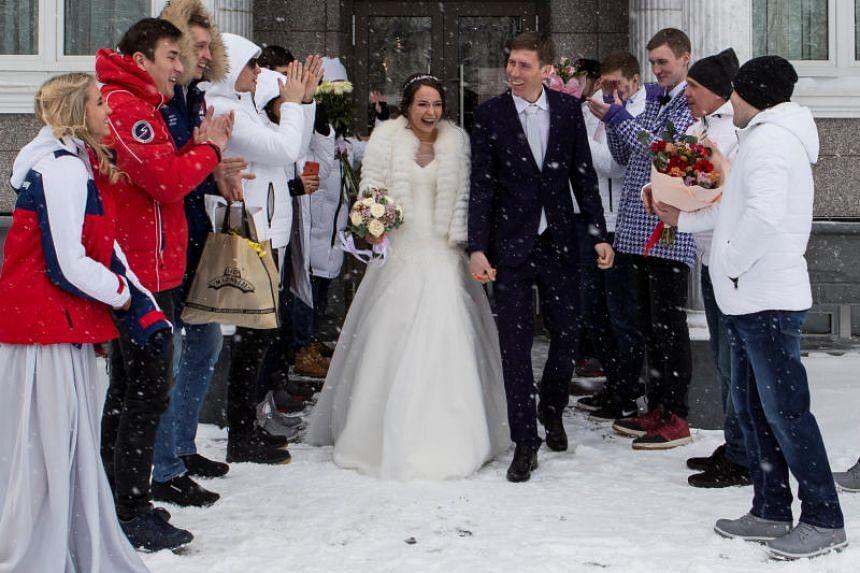 Russia's freestyle skier Semen Denshchikov and skeleton racer Olga Potylitsina leave the registry office after their wedding ceremony in Yuzhno-Sakhalinsk, Sakhalin island, Russia, on Feb 14, 2018.
