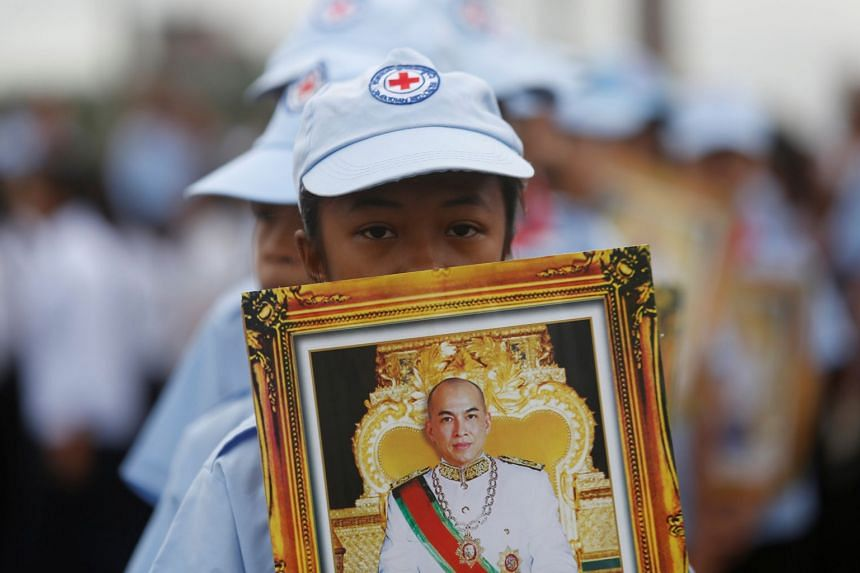 A student holding a portrait of King Norodom Sihamoni during the 64th anniversary celebration of the country's independence, in Phnom Penh on Nov 9, 2017.