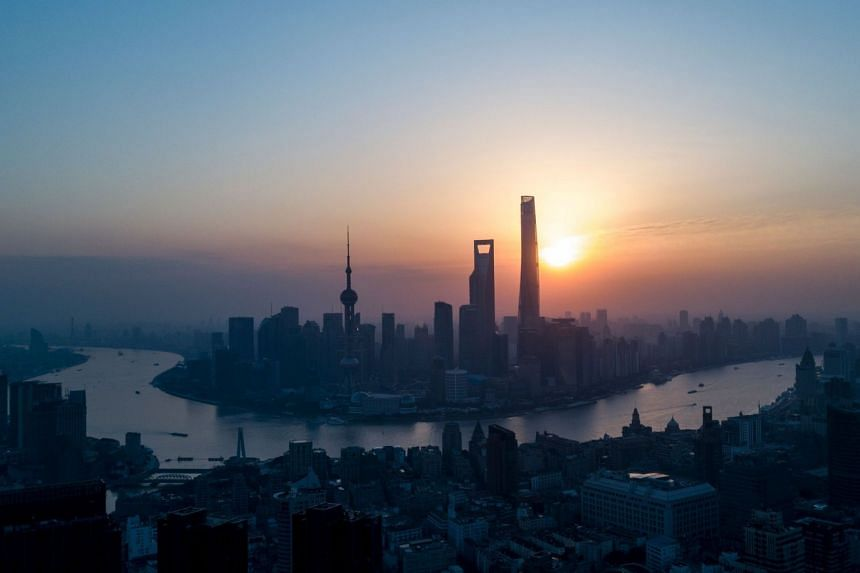 The sun rises over Shanghai's Lujiazui Financial District, along the Huangpu River, on Feb 4, 2018.