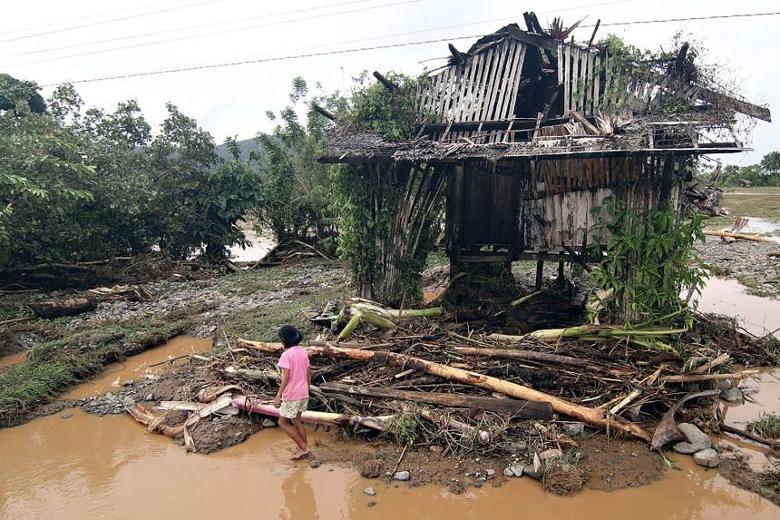 A resident walking past a house damaged by Tropical Storm Sanba in Jaboanga town, in Mindanao, on Feb 13, 2018.