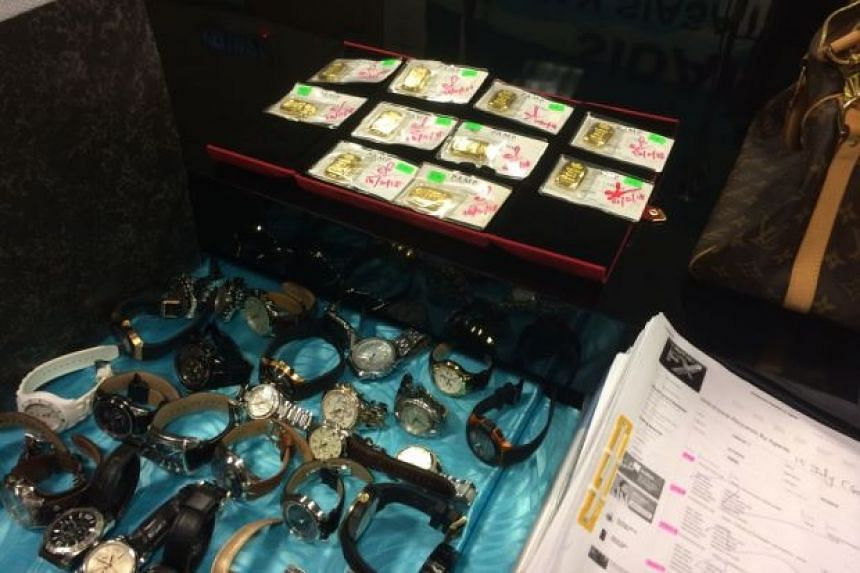 Luxury goods like watches, as well as cash and gold bars, were seized during the raids by Malaysian police.