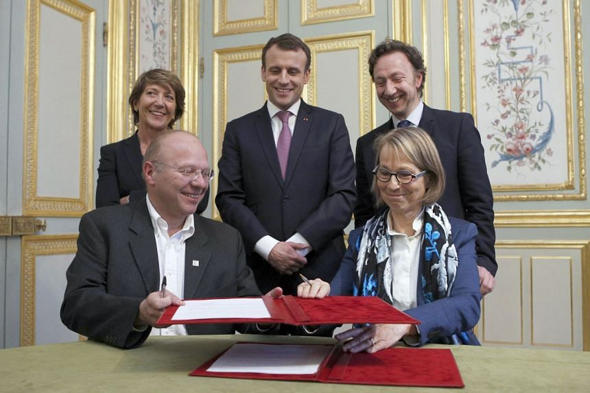 French Culture Minister Francoise Nyssen (seated, right) exchanges an agreement with President of the Heritage Foundation Guillaume Poitrinal (seated, left) as French President Emmanuel Macron (centre) look on during a cultural heritage agreement mee