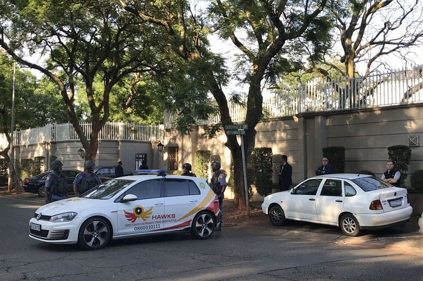 Members of the Hawks special police unit raid the compound of the Gupta family during an early morning raid in Johannesburg, South Africa, on Feb 14, 2018.