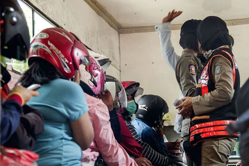Indonesian police officers detain unmarried couples (left, wearing helmets) after a raid in Surabaya on Feb 14, 2018.