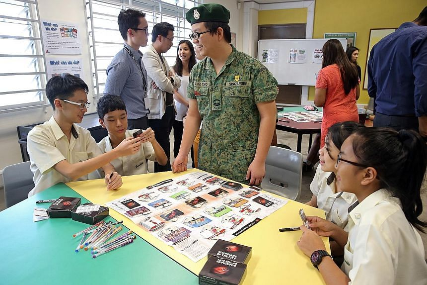 National Cadet Corps member Tan Ke Ting, 15, a Secondary 3 student at Greendale Secondary, teaching Secondary 2 students (from far left) Aidan Chiu and Jerick Chua, both 14, as well as Kimiko Alexandra and Hannah Tan, both 13, how to play Guardians o