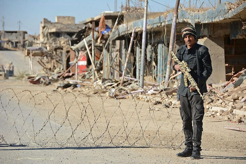 A member of the Iraqi forces guarding a checkpoint in the northern Iraqi city of Baiji. The one-time industrial hub has been reduced to a devastated ghost city in the fight against ISIS.