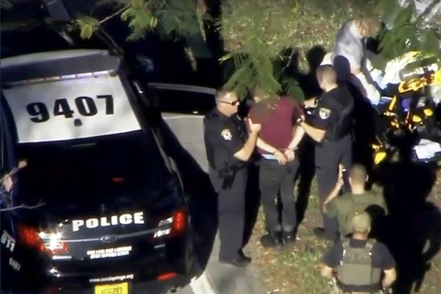 Police leading a man in handcuffs into a police car after a shooting at Marjory Stoneman Douglas High School, in Parkland, Florida, on Feb 14, 2018.