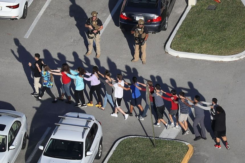 People are brought out of Marjory Stoneman Douglas High School in Parkland, Florida, after a shooting there on Feb 14, 2018.