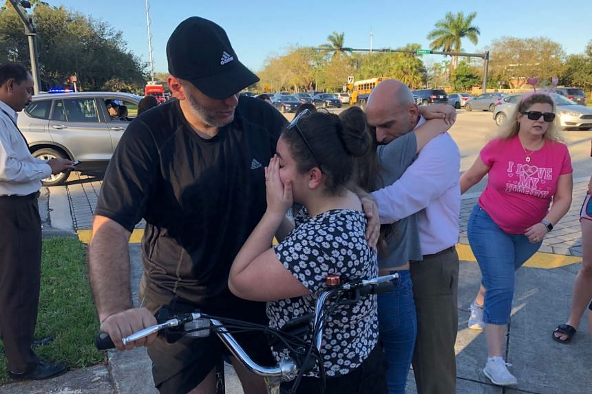 """People grieving outside Marjory Stoneman Douglas High School after a shooting caused """"numerous fatalities"""" in the school, on Feb 14, 2018."""