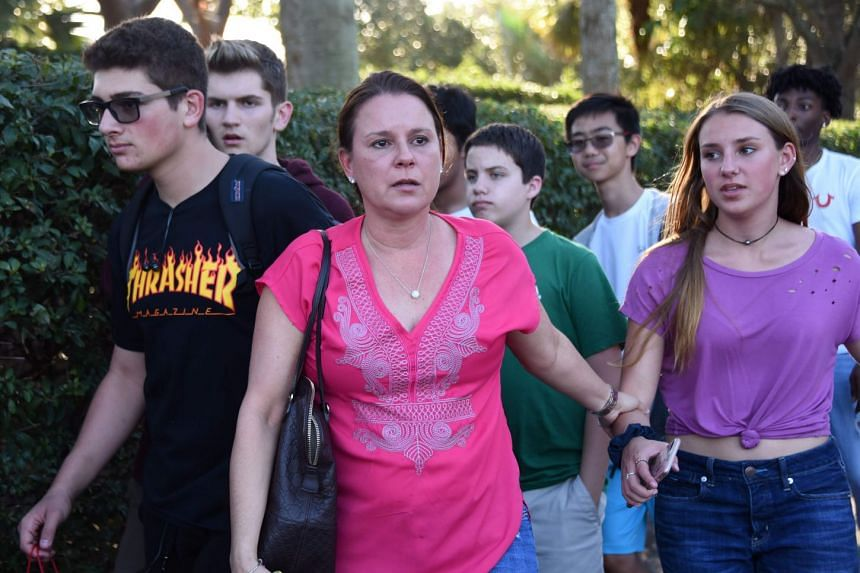 Students and adults leaving Marjory Stoneman Douglas High School, after a shooting incident, on Feb 14, 2018.