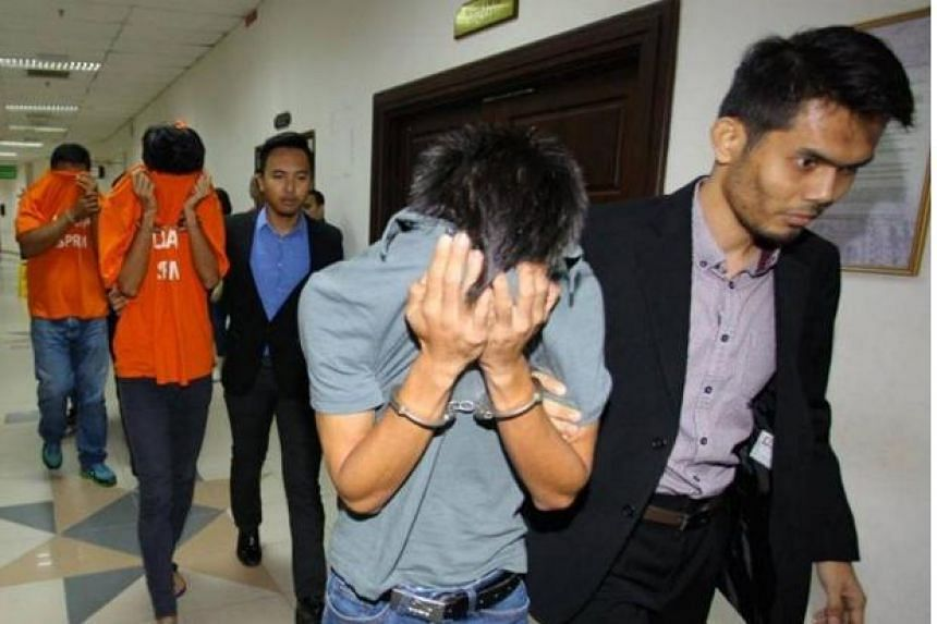 The three individuals are led to the magistrate's court.