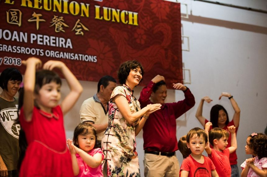 Grassroots Adviser Ms Joan Pereira (centre) joins the Henderson-Dawson Grassroots Leaders, volunteers from American Women's Association and children from Sam's Learning Centre at Henderson Community Centre to celebrate Chinese New Year.