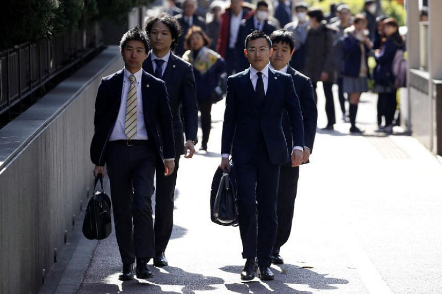 Lawyers representing a group of seven people who had invested in digital money at Coincheck, enter the Tokyo District Court to file a suit in Tokyo, on Feb 15, 2018.