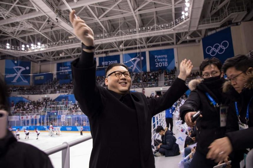 A man impersonating North Korean leader Kim Jong Un waves a unified Korean flag in front of North Korean cheerleaders attending the Unified Korean ice hockey game against Japan, on Feb 14, 2018.