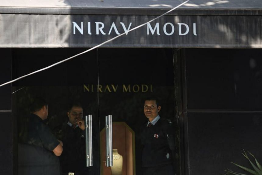 Indian security guards stand at the entrance of a Nirav Modi jewellery showroom in New Delhi, on Feb 15, 2018.