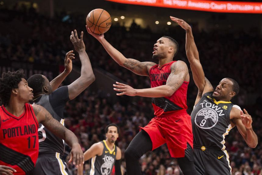 Portland Trail Blazers guard Damian Lillard drives to the basket against Golden State Warriors forward Andre Iguodala and forward Draymond Green for a score during the second half at the Moda Center.