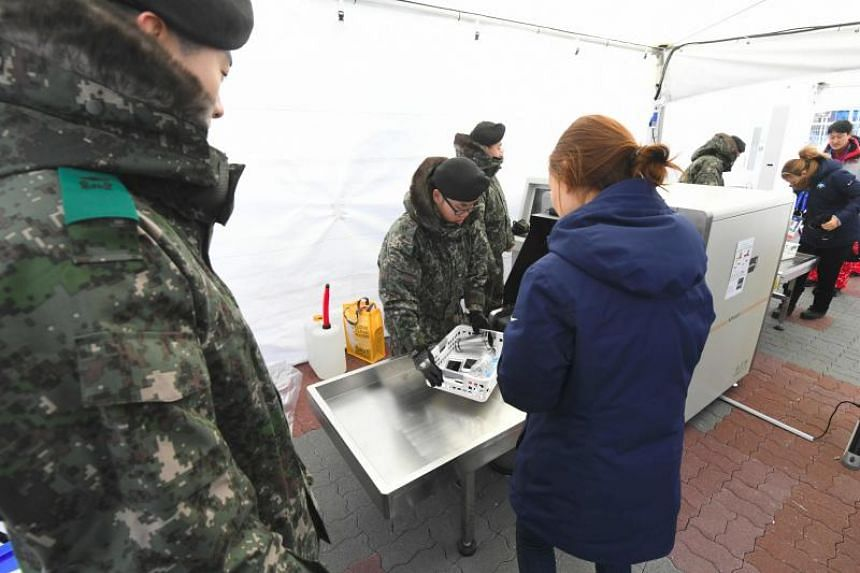 South Korean soldiers inspect a visitor at a security checkpoint as they replace security guards showing symptoms of the norovirus at the Gangneung Ice Arena in Gangneung on Feb 6, 2018 ahead of the Pyeongchang 2018 Winter Olympic Games.