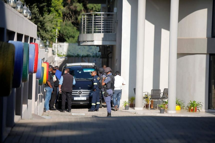 Police officers are seen inside the compound of the Gupta family in Johannesburg, Feb 14, 2018.