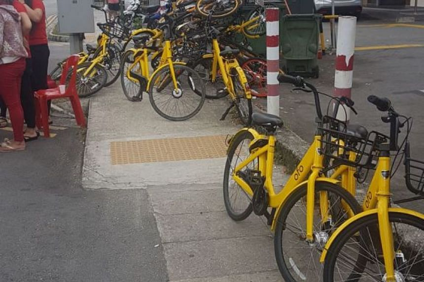 The pedestrian walkway along the road blocked with a stack of ofo bicycles.