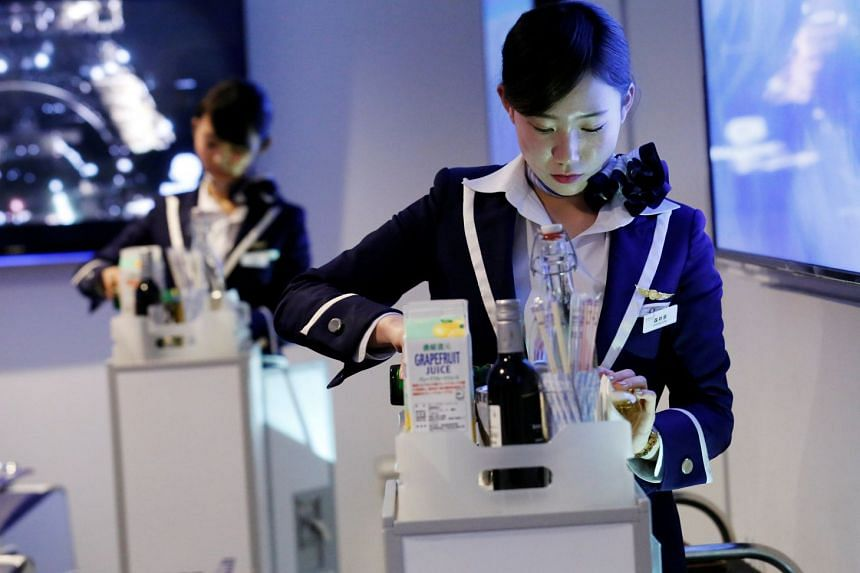 Staff dressed as flight attendants, serve drinks to guests at the First Airlines, virtual first-class airline experience facility in Tokyo, Japan, on Feb 14, 2018.