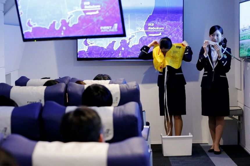Staff dressed as flight attendants, perform a safety demonstration at the First Airlines, virtual first-class airline experience facility in Tokyo, Japan, on Feb 14, 2018.