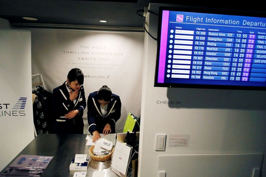 """Staff dressed as flight attendants working at a counter for First Airlines while """"flight"""" times are displayed on a screen, at the First Airlines facility in Tokyo on Feb 14, 2018."""