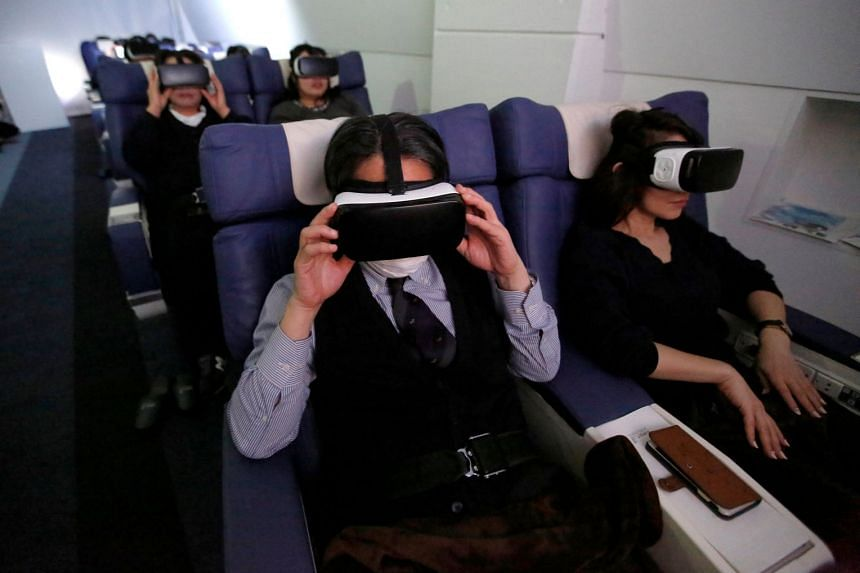 Guests wearing virtual reality (VR) goggles are seen at the First Airlines, virtual first-class airline experience facility in Tokyo, Japan, on Feb 14, 2018.