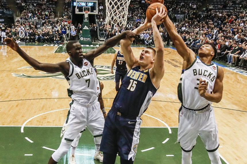 Denver Nuggets centre Nikola Jokic (centre) shoots between Milwaukee Bucks centre Thon Maker (left) and forward Giannis Antetokounmpo  in the first half of the game.