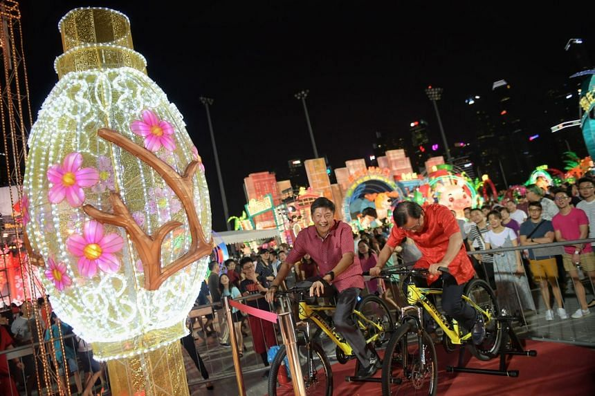 Mr Ng Chee Meng cycling on a roller that powers up a display at the event.