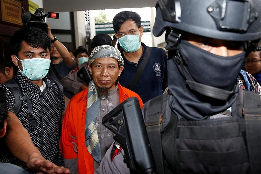 Aman Abdurrahman being guarded by police officers on his way to the courtroom yesterday. He faces the death penalty if found guilty of the various charges against him.