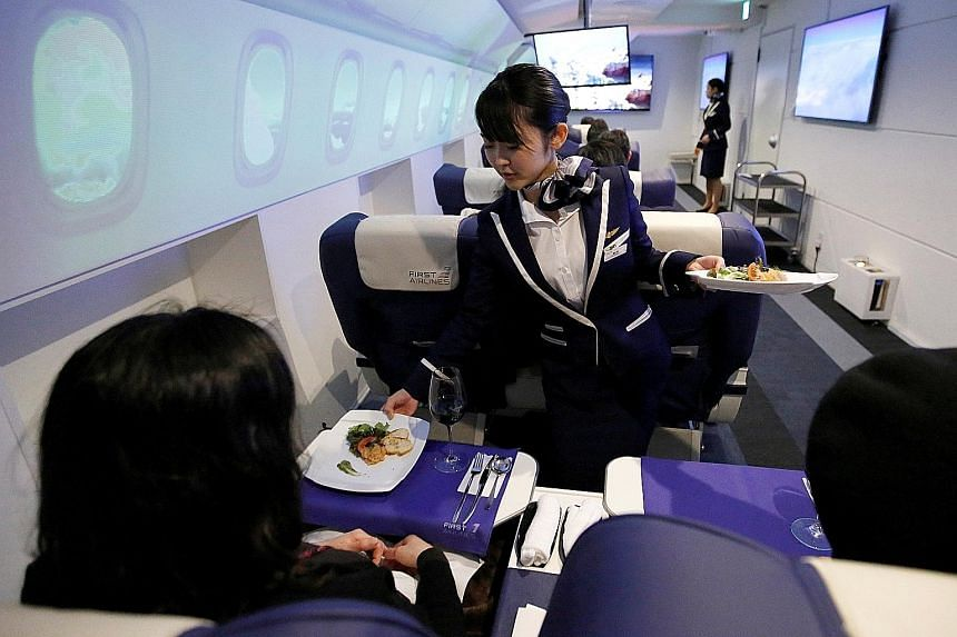 An employee, dressed as a flight attendant, serving appetisers to guests on First Airlines, a virtual first-and business-class airline experience facility in Tokyo. The Japanese company is offering trips to Paris on flights that never leave the groun