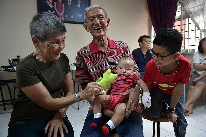 Mr Ng Ghim Tin, 82, and his wife Lim Lay Hin, 78, with their great grandson Ethan and grandson Caleb, 10. All 18 family members gathered for their reunion dinner in Pasir Ris last night in a Chinese New Year tradition. This year, the Ngs celebrated t