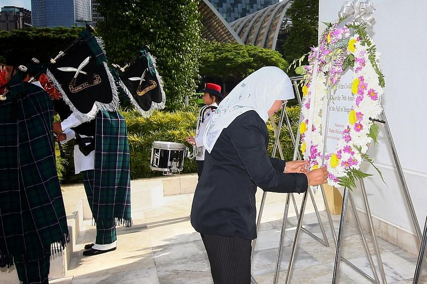 Above: President Halimah Yacob, guest of honour at the 51st War Memorial Service, laying a wreath at the War Memorial Park on Total Defence Day yesterday. Right: Guests at yesterday's service paying their respects at the Civilian War Memorial, which