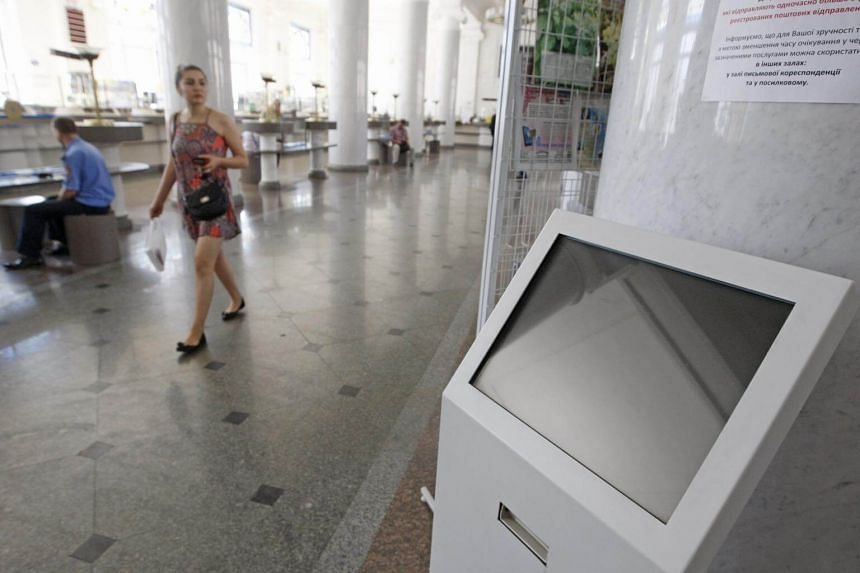 A file photo of a woman walking past an affected terminal, at main post office of Ukrainian State Enterprise of Posts 'Ukrposhta', after Ukrainian institutions were hit by a wave of cyber attacks day earlier, on June 28, 2017.