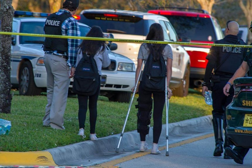 Emergency personnel aid students at the scene of a shooting at Marjory Stoneman Douglas High School in Parkland, Florida, on Feb 14, 2018.