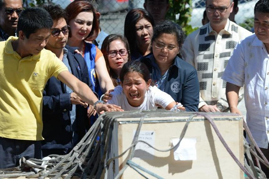 Jessica (centre), sister of Filipina worker Joanna Demafelis whose body was found inside a freezer in Kuwait, cries in front of a wooden casket containing her sister's body shortly after its arrival at the international airport in Manila on Feb 16, 2