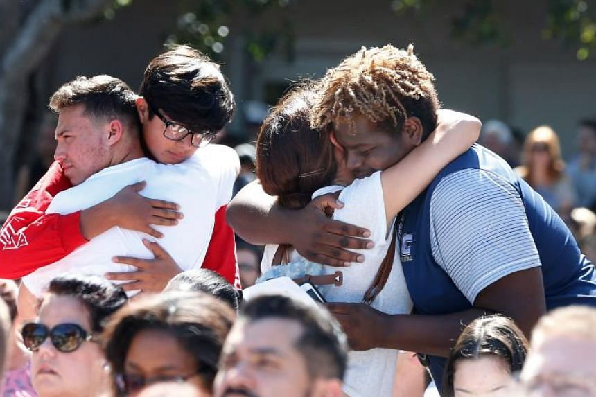Mourners hug during a prayer vigil for the victims of the Marjory Stoneman Douglas High School shooting at Parkridge Church in Coral Springs, Florida on Feb 15, 2018.