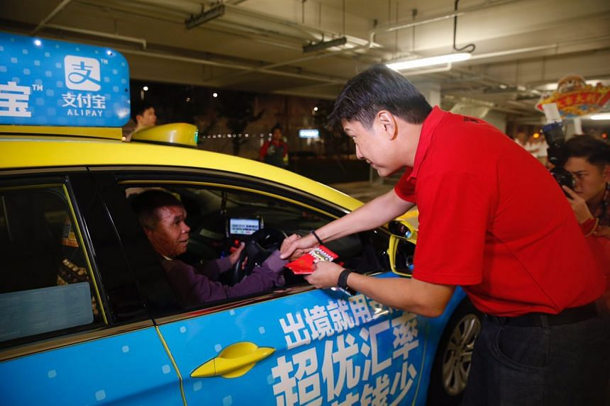 Second Minister for Transport Ng Chee Meng greeting a taxi driver at Changi Airport Terminal 4. During the visit, more than 1,000 taxi drivers and airport staff received gift bags prepared by the National Taxi Association.