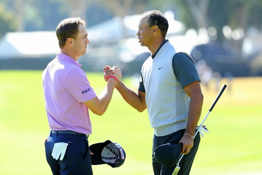 Justin Thomas and Tiger Woods shake hands after finishing their round.