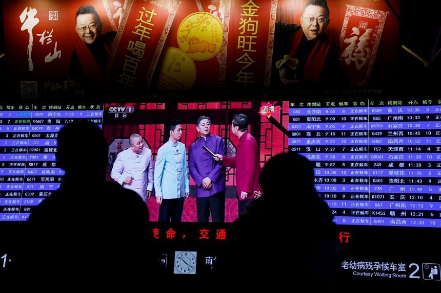 People watch the CCTV Spring Festival Gala TV show on a screen at the Beijing West train station in Beijing, China, on Feb 15, 2018.