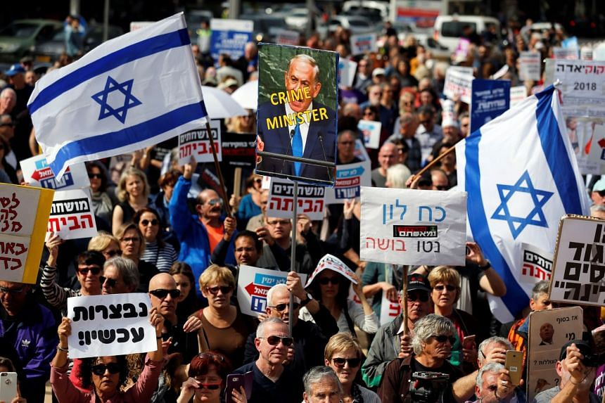 Protesters hold signs calling on Netanyahu to step down during a rally in Tel Aviv.
