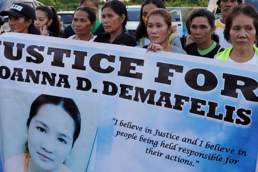 Residents display placards as they wait for the arrival of the body of Joanna Demafelis, a Filipina domestic helper who was killed and found inside a freezer in Kuwait, in her hometown in Iloilo province in the Philippines on Feb 17, 2018.