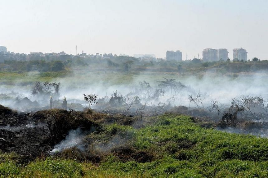 Indian firefighters try to douse a fire at Bellandur Lake in Bangalore on Jan 20, 2017. Rampant population growth has left some of its famous lakes so polluted that they regularly catch fire spontaneously.