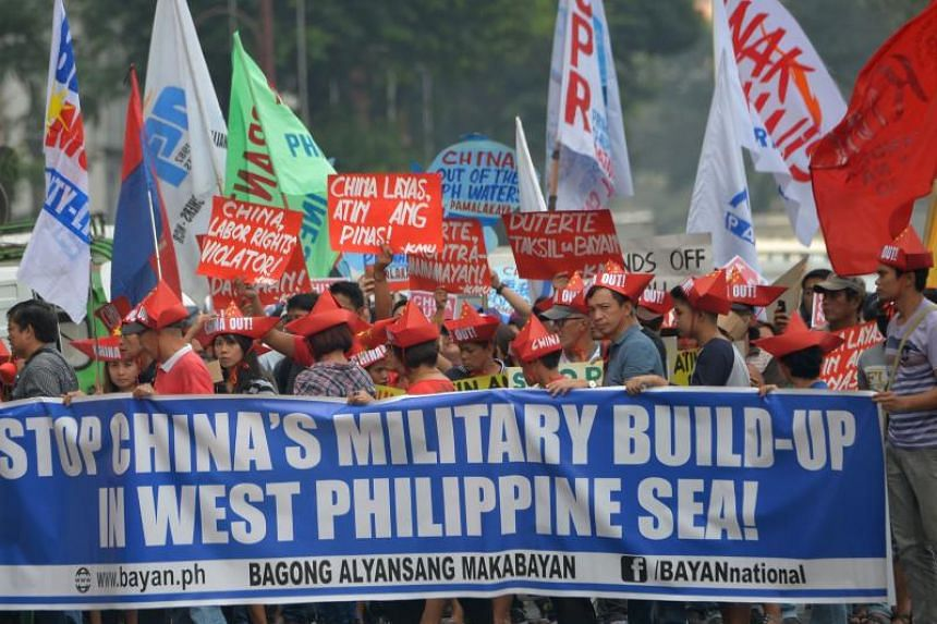 Activists carry placards during a protest in front of the Chinese consulate in Manila on Feb 10, 2018.