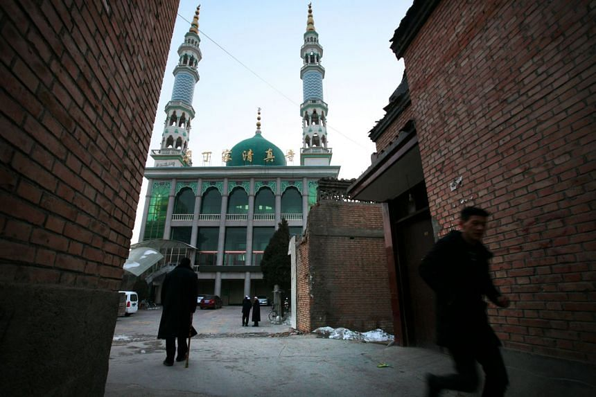 A man runs in front of a mosque at dusk as evening prayers are underway inside, in Linxia, China, home to a large population of ethnic minority Hui Muslims on Feb 2, 2018.