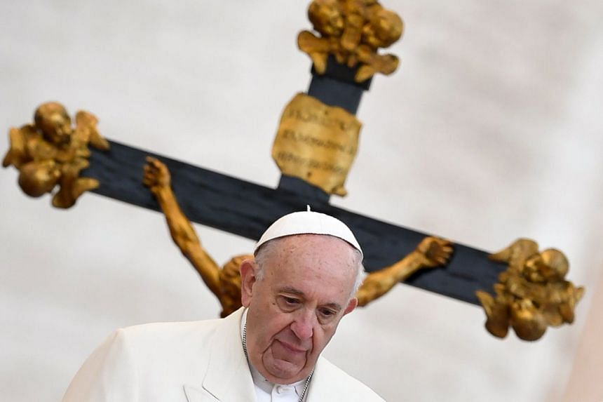 Pope Francis standing in front of a crucifix during his weekly general audience at St Peter's Square.